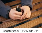 Small photo of Young adult man outside and smoking tobacco device electronic cigarette heater. Smoke and steam system with sticks inside, image with copy space. Harmful habit harm to health lungs