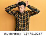 Small photo of Young hispanic man wearing casual clothes doing bunny ears gesture with hands palms looking cynical and skeptical. easter rabbit concept.