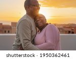 Small photo of Happy Latin senior couple having romantic moment embracing on rooftop during sunset time - Elderly people love concept