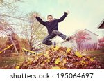 Boy Jumping In A Pile Of Autumn ...