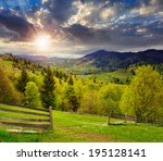 summer landscape. fence near the meadow path on the hillside. forest in fog on the mountain at sunset - stock photo