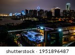 Haikou cityscape with rooftop terrace and view on the coastal city bay and skyline illuminated at night in Haikou Hainan China