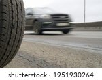 Small photo of A stationary wheel against the background of a fast moving car. Speed concept. An example of contradistinction is immobility and movement.
