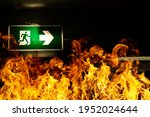 Small photo of Green fire escape sign hang on the ceiling in the Warehouse. The concept of fire escape training and preparation for evacuation