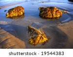 A rock pool with three boulders - stock photo