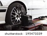 Small photo of suspension adjustment and automobile wheel alignment work at repair service station
