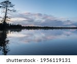 Swamp lake photo taken during sunset. Calm weather with not wind. Perfect reflection on the mirror clear lake water. Single tree on the side of the image. Darker image vibes. Nice strong clouds