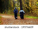 Kids in a park on a sunny but cold autumn day - stock photo