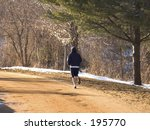 Country Road Runner  This is a shot of a runner along a dirt road through the country. - stock photo