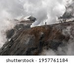 Climbing tourists to the Mutnovsky volcano. Tourists admire the view of the snow-capped mountains of the volcano and the steam coming out of the fumaroles. Kamchatka Peninsula, Russia.