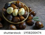 Small photo of Fresh Waive fruit in Bamboo basket on wooden table, Fresh Salak or Snake Fruit tropical fruit on a wooden table.