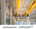 Small photo of Overhead crane inside factory or warehouse. That industrial machinery or lifting equipment consist of hoist, hook and wire rope traveling on beam girder structure. For manufacturing production plant.