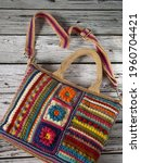Small photo of Image of colorful crochet bag made of leftover yarn. Isolated against wooden surface. Concept of creativity, something bright, colorful, and utilization leftover things.