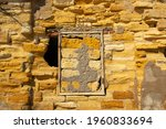Yellow natural sandy stone brick old ruined house wall with closed window
