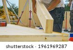 Small photo of CLOSE UP, DOF: Unrecognizable male builder picks up a CLT beam from a workbench at an unfinished housing project. Contractor carries a glued laminated board across the bustling construction site