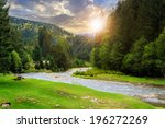 camping place on rocky shore of mountain river near the forest at sunset - stock photo