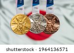 Small photo of April 25, 2021 Tokyo, Japan. Gold, silver and bronze medals of the XXXII Summer Olympic Games 2020 in Tokyo on the background of the flag of Japan.