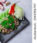 "Small photo of Minced pork larb served with fresh vegetables, a popular Thai food in the Northeast. In Thai, it is smoother than ""Larb Moo""."