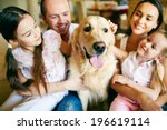 Stock photo a young friendly family of four cuddling their pet 196619114