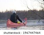 Man Rowing A Canoe In Early...