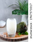 Small photo of A Glass of Es Sirsak or Soursop or Guanabana Juice with Selasih or Basil Seeds and Nata de Coco on a wooden board with fruit and leaf ornament.