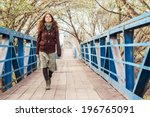 Small photo of Young girl walking over the bridge in early spring