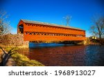 Small photo of Wooden covered bridge over the river. Red wooden covered bridge. Covered bridge over river