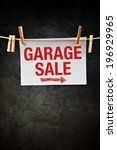 Small photo of Garage Sale sign attached to rope with clothes pins.
