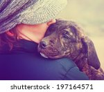Stock photo a girl holding a pit bull mix puppy done with a retro vintage instagram filter 197164571