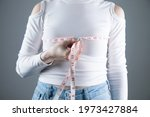 Small photo of young girl measures breast girth on a gray background