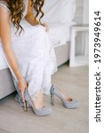 Bride Sits On Bed And Puts On...