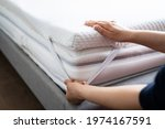 mattress topper being laid on... | Shutterstock . vector #1974167591