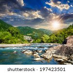 mountain river with stones in the forest near the metal bridge at sunset - stock photo