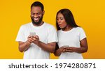 Small photo of Portrait of shocked African American woman spying on her smiling boyfriend who using mobile phone, texting sms or scrolling social media news feed. Black couple standing over yellow studio background