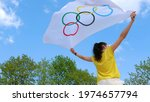 Small photo of Riga. Latvia May 16, 2021. Woman fan in yellow t-shirt holding flapping in wind flag of five rings symbol of Olympic Games. Sports, Entertainment and Sport Fan Concept