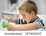 child painting a ceramic... | Shutterstock . vector #197605547