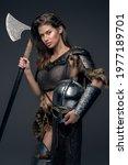 Small photo of Studio shot of warlike female viking with axe