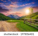 unreal summer landscape. fence near the meadow crossroad path on the hillside composite with forest on the mountain at sunset  in light flare - stock photo
