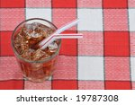 Glass of soda with straws on checkered table cloth - stock photo