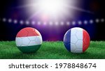 Two soccer balls in flags colors on stadium blurred background. Hungary and France. 3d image