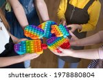 Small photo of children brought to kindergarten a popular toy pop it, hold in their hands anti-stress, silicone game
