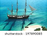 Exploration, A pirate or merchant ship anchored next to an island with the crew going ashore. - stock photo