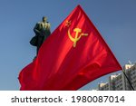 The flag of the Soviet Union (USSR) waving in the wind against the background of the monument to Lenin. Monument to the communist leader Lenin in the rays of the setting sun.