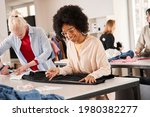 Small photo of Woman looking attentively at the clothes and thinking how to redo