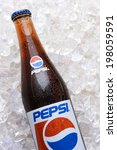 "Small photo of IRVINE, CA - JUNE 9, 2014: Closeup of a bottle of Pepsi soda in ice. Originally named ""Brad's Drink"" it was later changed to Pepsi Cola after the digestive enzyme pepsin and kola nuts in the recipe."