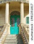 Small photo of A traditional Maltese wooden door, painted cyan, and limestone facade of a traditional old Maltese house.Typical maltese architecture. Building exterior.Birzebugga
