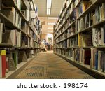 This is a shot of some book shelfs and some students studying in the local library. - stock photo