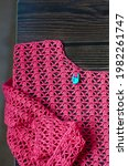 Small photo of Crocheting with pink cotton threads on a dark wooden background. Crochet process with pink cotton yarn. Crochet patterns on the wooden table. Crochet needlework close-up.