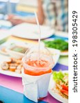 Small photo of ake away glass of fresh orange juice on the colorful wood table