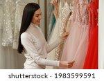 Woman Choosing Dress In Rental...